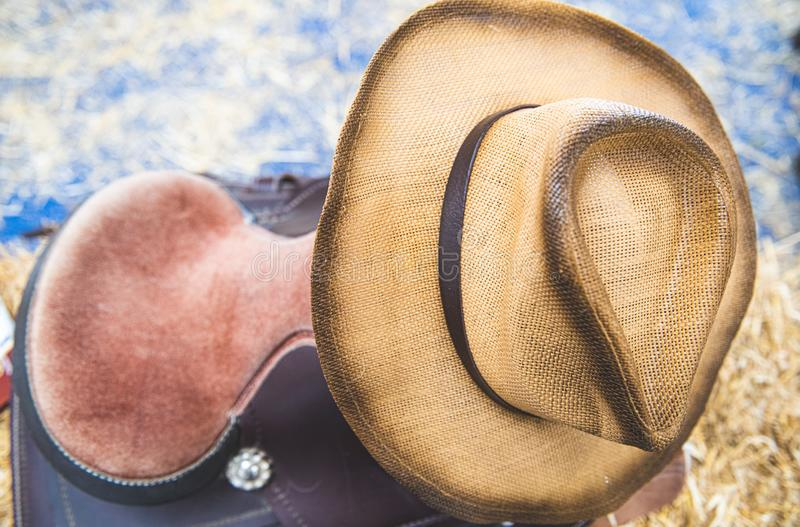 Cowboy horse riding saddle and hat personal equipment. Close-up of cowboy hat and horse saddle in a store on tumbleweed straw bale, american style riding stock images