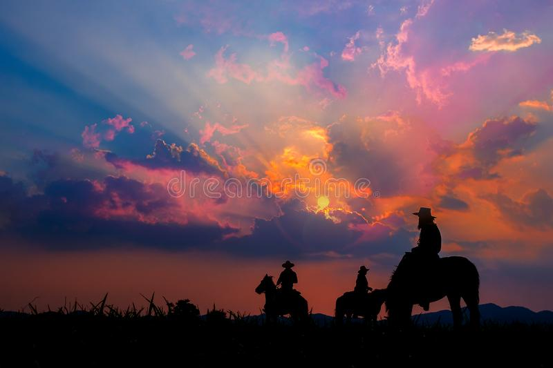 Cowboy on horseback with views of the mountains and sunset sky. Cowboy on horseback with views of the mountains and the sunset sky royalty free stock photo