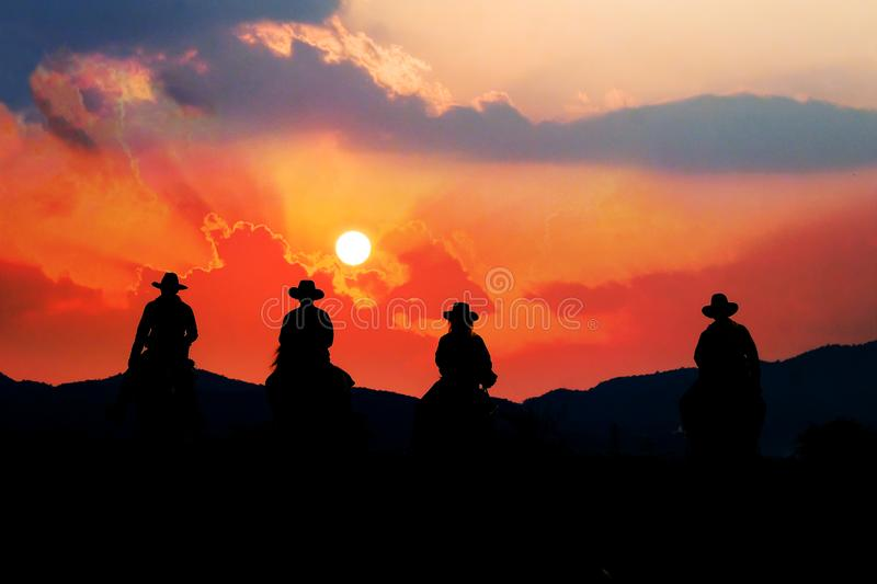 Cowboy on horseback with views of the mountains and sunset sky. Cowboy on horseback with views of the mountains and the sunset sky stock image