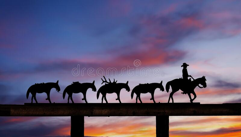 Cowboy and horses silhouettes at the gate of a ranch at sunset royalty free stock photography