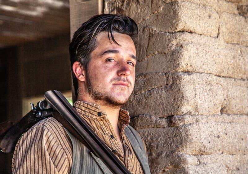 Cowboy im Eingang mit Gewehr bei altem Tucson stockfotografie