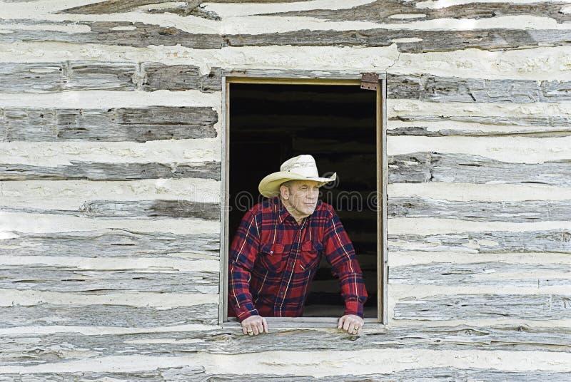 Cowboy Looking Out une fenêtre images stock