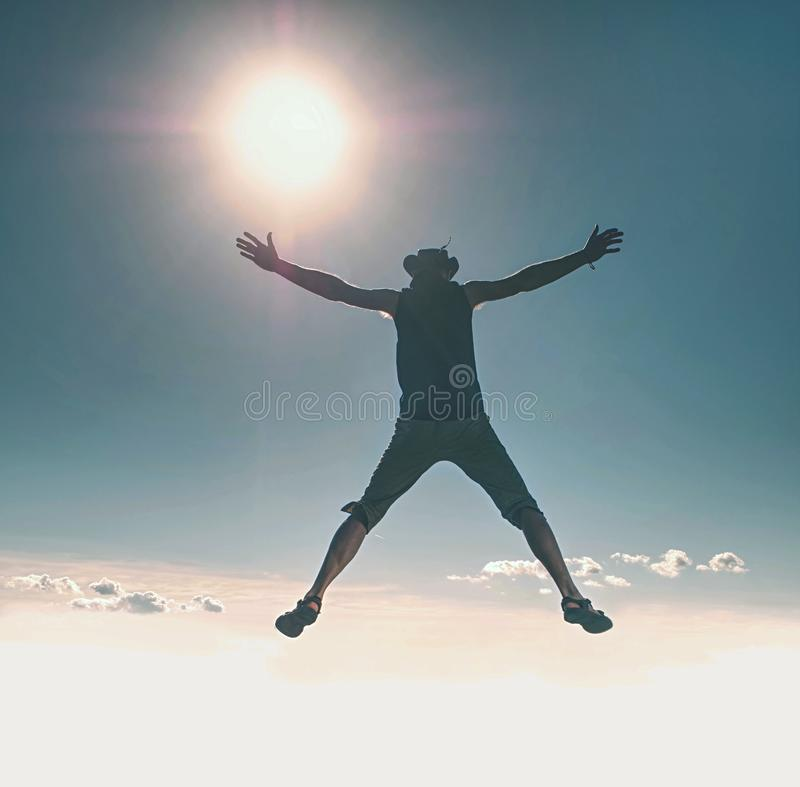 Cowboy man sky diving. Young crazy man is jumping above landscape royalty free stock photo