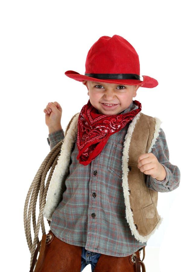Cowboy mignon d'enfant en bas âge souriant tenant une corde utilisant un chapeau rouge images stock