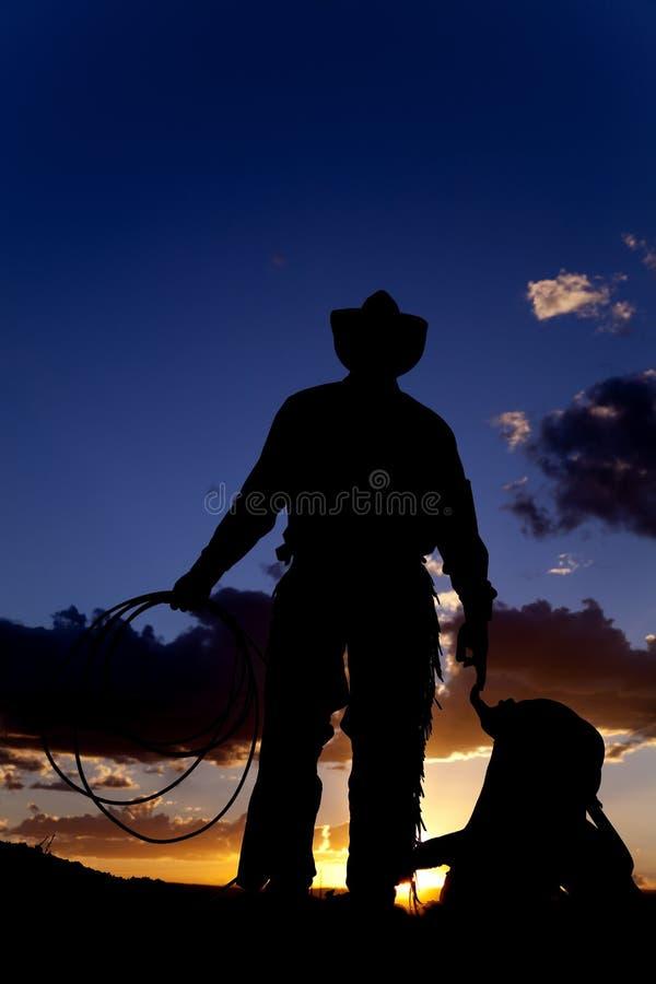 Cowboy mit Sattel auf dem Boden stockbild