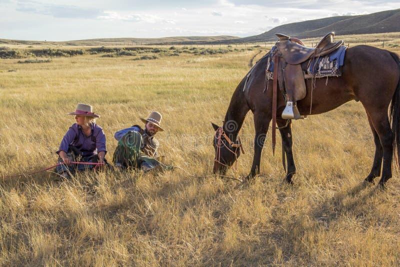 Cowboy och cowgirl vid hästen fotografering för bildbyråer