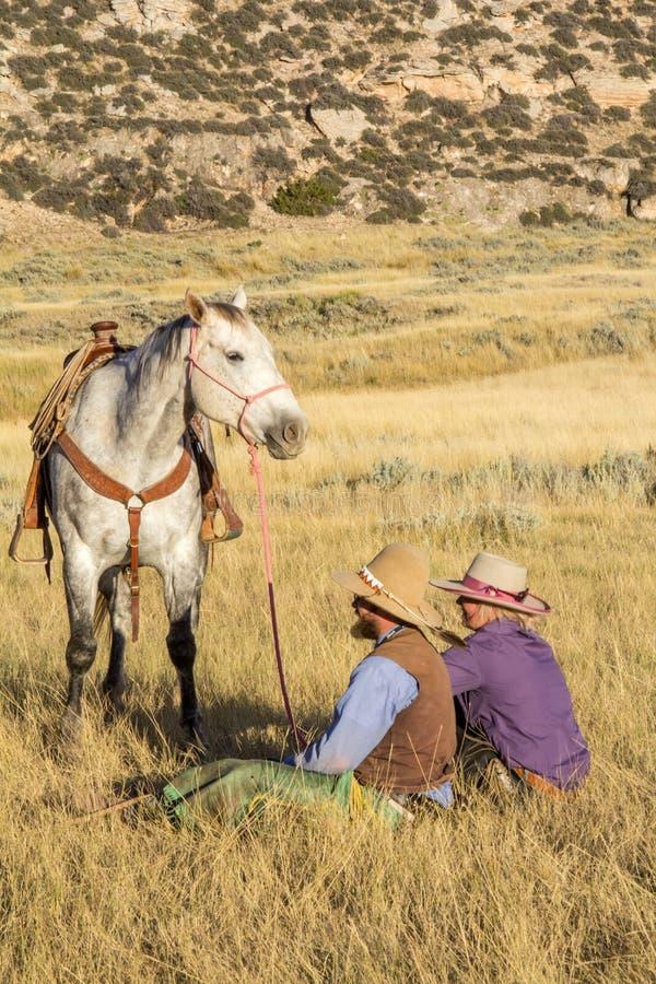 Cowboy- och cowgirlsammanträde i hållande häst för gräs fotografering för bildbyråer