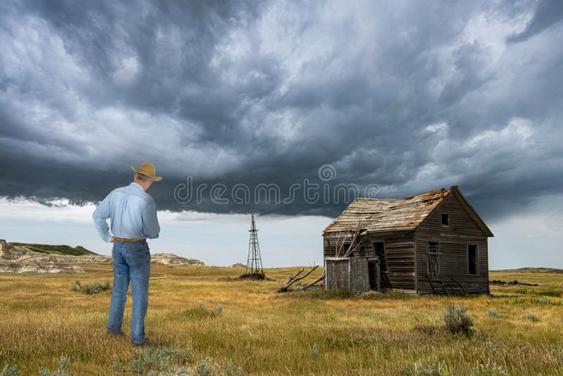 Cowboy, Old Prairie Cabin, Ranch. A cowboy stands on the prairie by his old vintage cabin. The retro cattle ranch is on the plains royalty free stock photos
