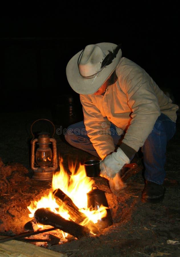 Cowboy pelo incêndio antes do alvorecer imagens de stock royalty free