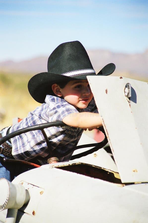Cowboy pequeno que trabalha em um trator imagens de stock royalty free