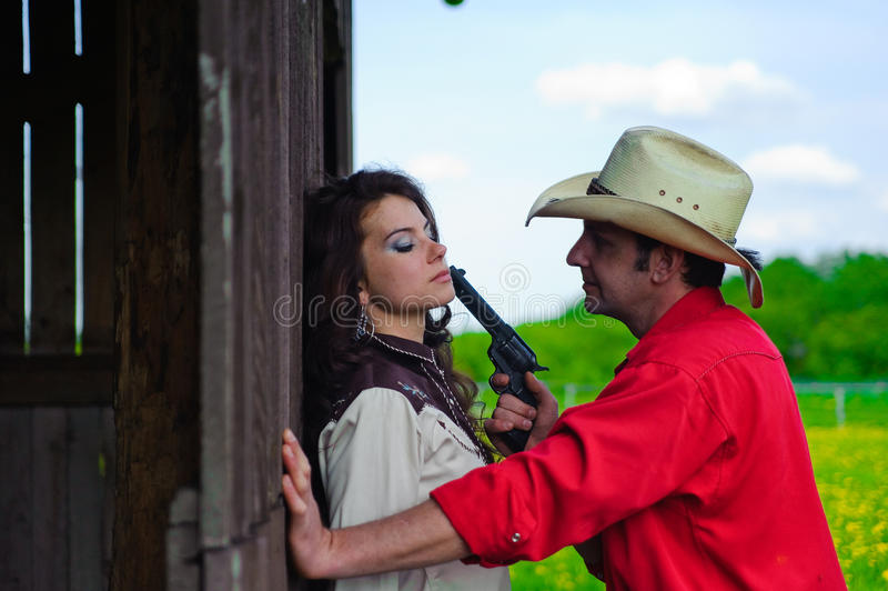 The cowboy with a pistol in hands. The cowboy with a revolver in hands menacing to the woman stock image