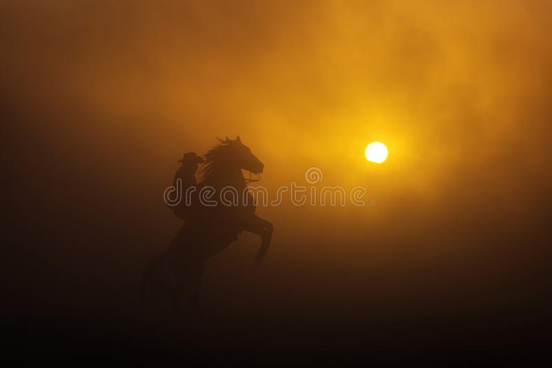 Cowboy puting his horse to stay in two feets at sunset with dust in background.  stock photography