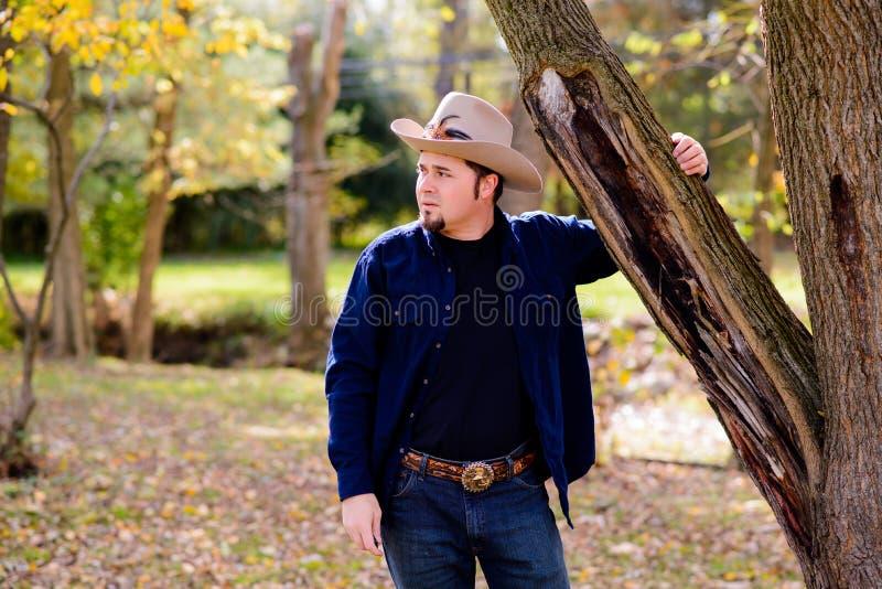 Cowboy Rancher all'albero che guarda a sinistra immagini stock libere da diritti