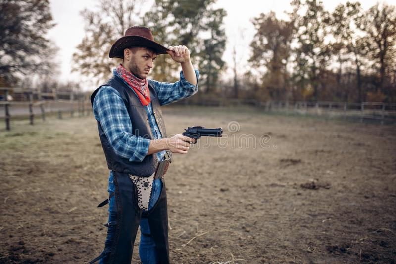 Cowboy with revolver, gunfight on ranch, western. Cowboy with revolver, front view, gunfight on texas ranch, western. Vintage male person with gun, wild west stock photos