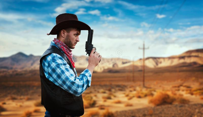 Cowboy with revolver, gunfight in gesert valley. Cowboy with revolver prepares to gunfight in gesert valley, western. Vintage male person with gun, wild west royalty free stock photos