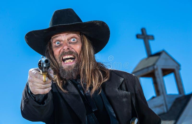 Cowboy riant avec l'arme à feu photographie stock libre de droits