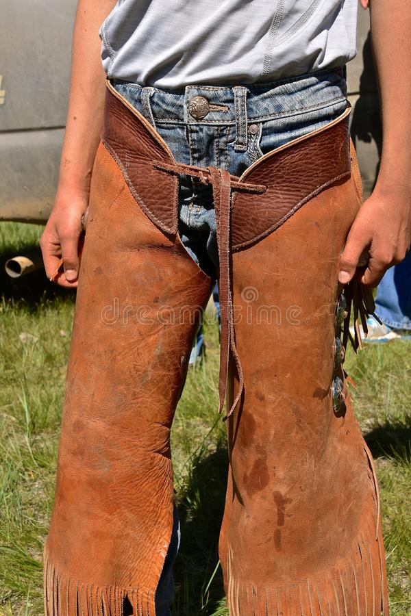 Cowboy in riding chaps at a roundup. An unidentified cowboy in riding chaps is prepared for a roundup and branding session on a ranch royalty free stock image