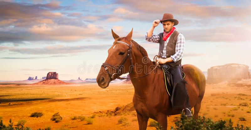 Cowboy riding a horse in desert valley, western stock image