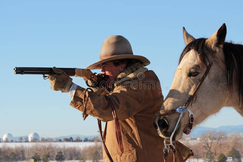 Cowboy With a Rifle. A cowboy against a bright blue sky. He's aiming a rifle off to the side of the photo royalty free stock photography