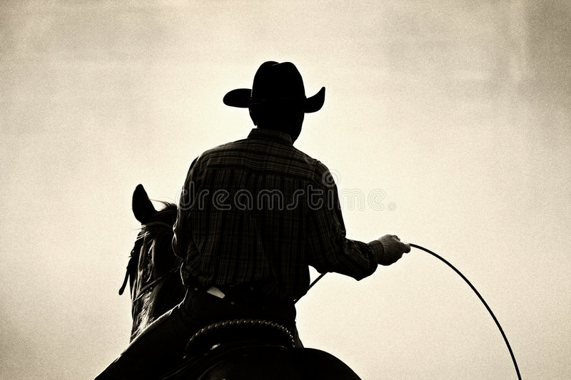 Cowboy rodeo. Cowboy at the rodeo - shot backlit against big cloud of dust, converted with added grain royalty free stock images