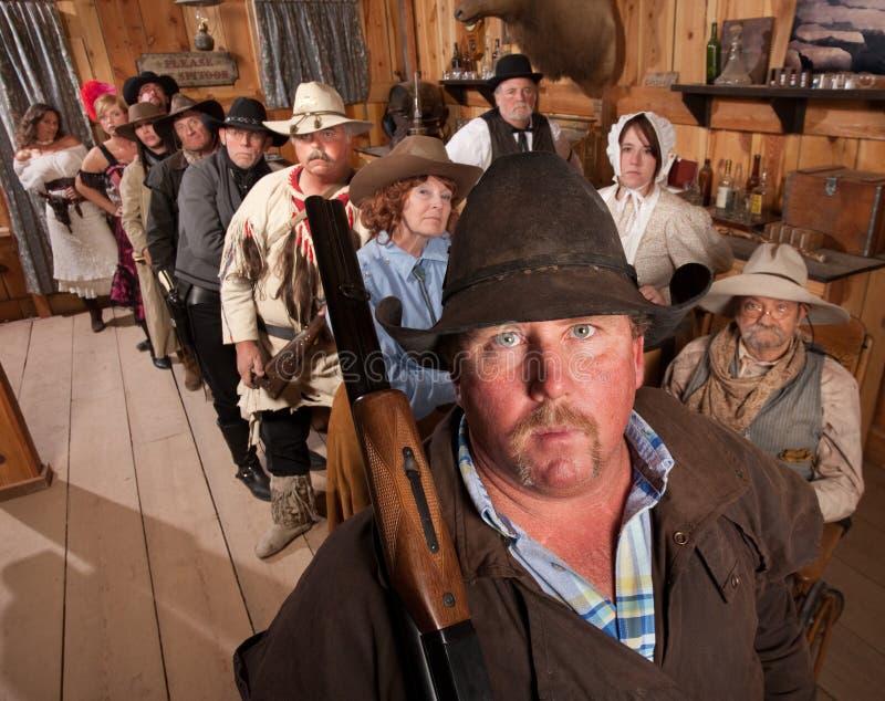 Cowboy sério com o rifle no bar foto de stock royalty free