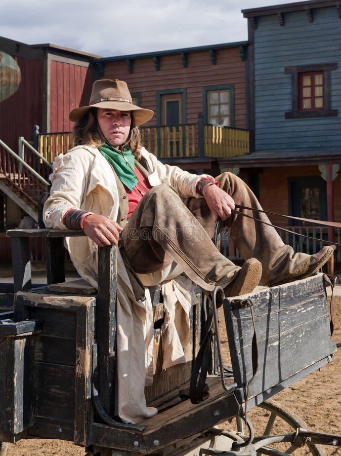 Cowboy s'asseyant sur un chariot images stock