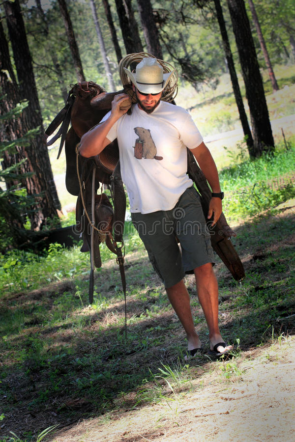 Cowboy with Saddle. An informal unshaven cowboy wearing a white straw western hat carrying a saddle. Trees in background. Shallow depth of field. Image tilted stock image