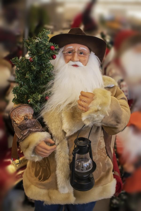 Cowboy Santa Claus in shearling coat with saddle and lantern and Christmas tree - selective focus - blurred background stock photos