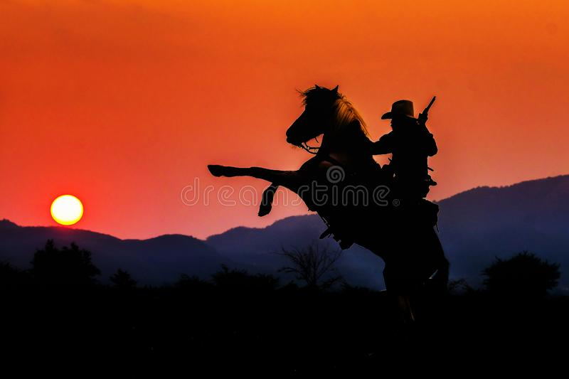 Cowboy silhouette on horse during nice sunset. Cowboy silhouette on a horse during nice sunset royalty free stock image