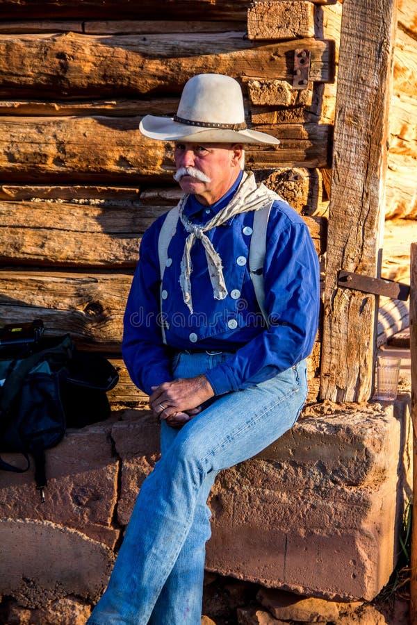 Cowboy Sitting al granaio fotografia stock libera da diritti