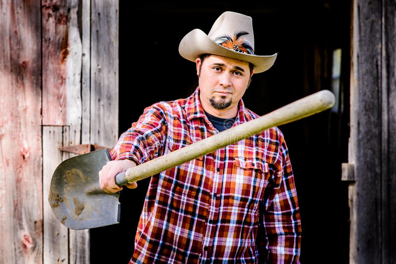 Cowboy Smirking and Handing Shovel to you royalty free stock images