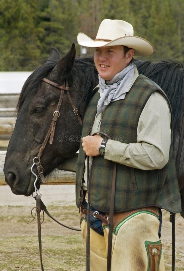 Cowboy sorridente che tiene la testa del suo cavallo fotografia stock