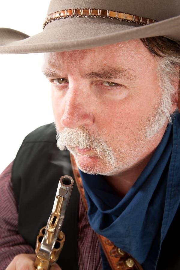 Cowboy soufflant sur l'extrémité d'un pistolet chaud image libre de droits