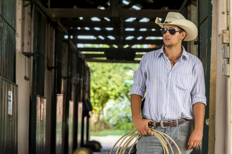Cowboy on stable. With lasso royalty free stock photography