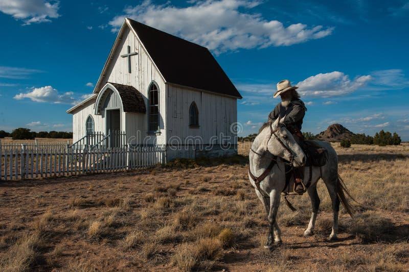 Cowboy steht sein Pferd vor einer alten Kirche im ländlichen Gebiet des New Mexiko still lizenzfreie stockfotografie