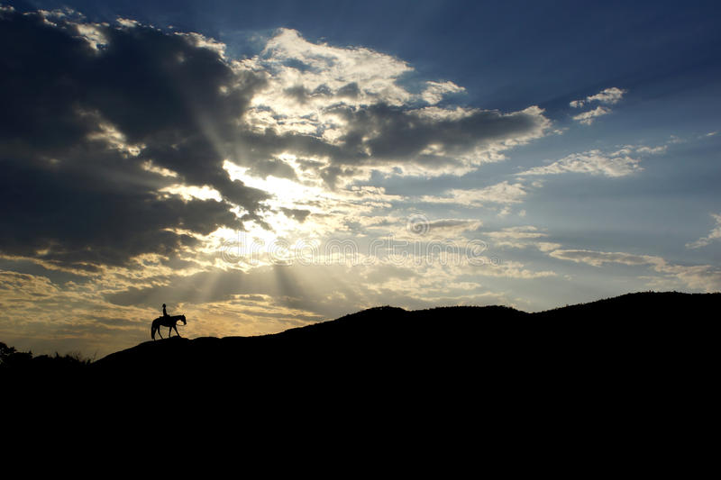 Cowboy at sunset. Cowboy riding horse silhouette at sunset with cloud blue sky stock photos