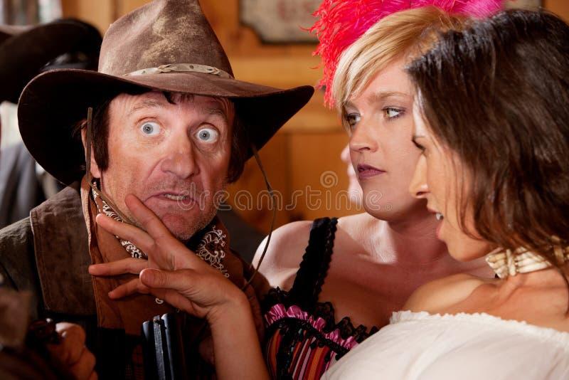 Cowboy surpreendido e duas mulheres encantadoras fotografia de stock royalty free