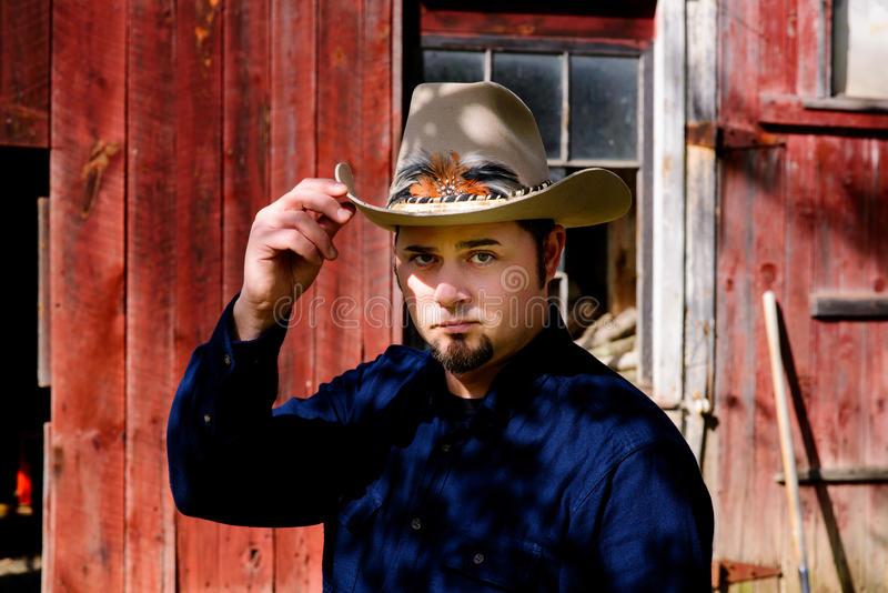 Cowboy Tipping Hat in front of Barn royalty free stock image