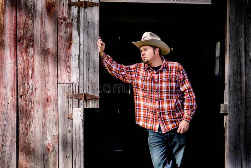 Cowboy Waiting for Someone at Barn Door royalty free stock images