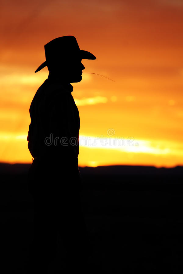 Cowboy Watching the Sunset. Silhouette of a cowboy watching the a beautiful New Mexico sunset while chewing on a piece of grass stock photos