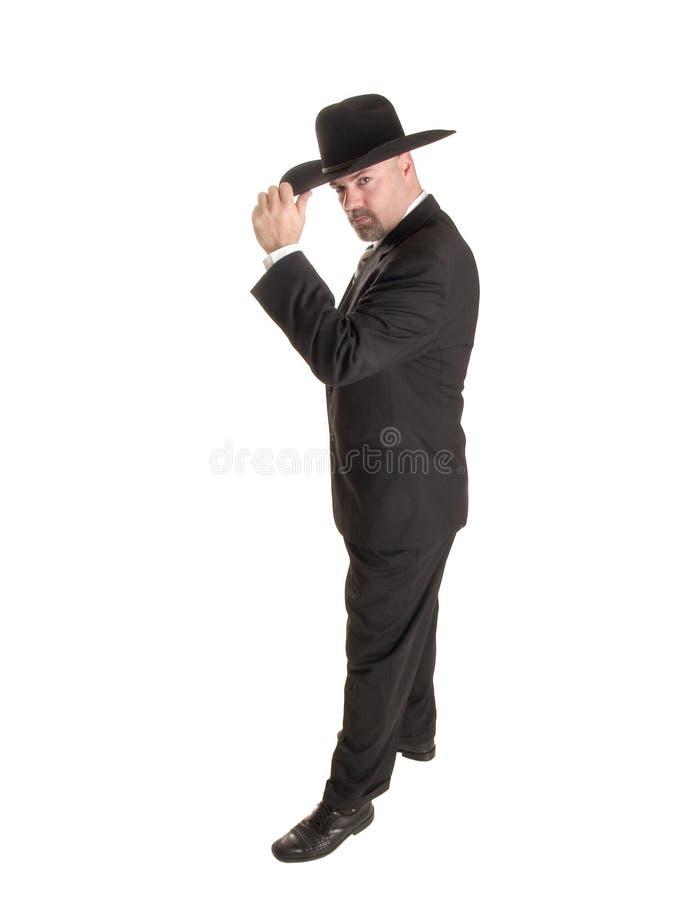 Cowboyaffärsman som tippar hatten royaltyfri foto
