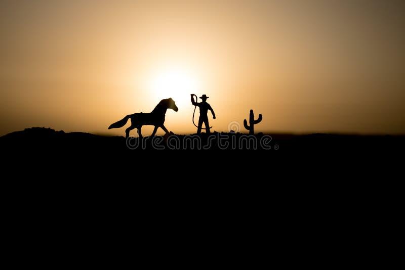 Cowboyconcept Silhouet van Cowboys in zonsondergangtijd Cowboyssilhouetten op een heuvel met paarden royalty-vrije stock foto's