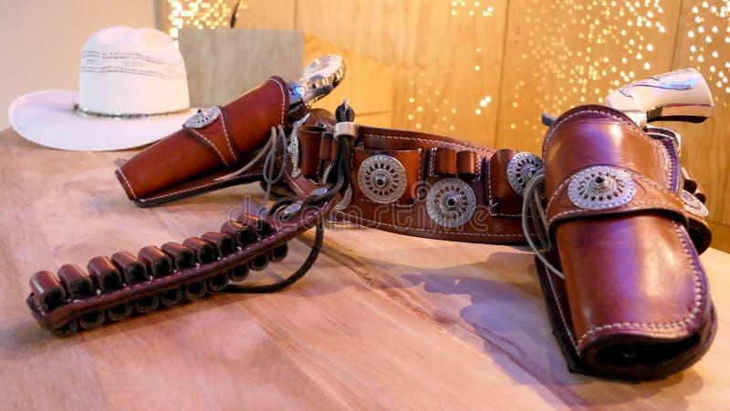 Cowboyhatt, vapen, pistoler, bälten arkivfoto