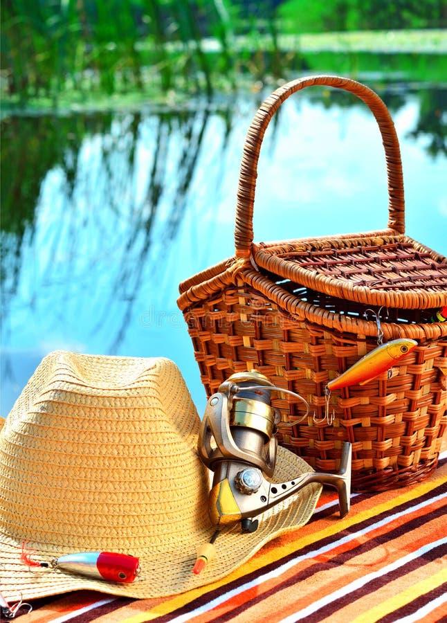 Cowboyhoed, rieten mand, spoel andfishing uitrusting in natur stock foto's
