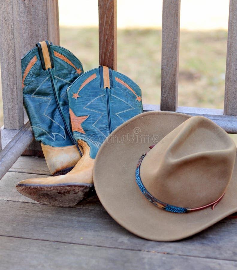 Cowboyhut und Matten, die an einem Geländer sich lehnen lizenzfreies stockbild