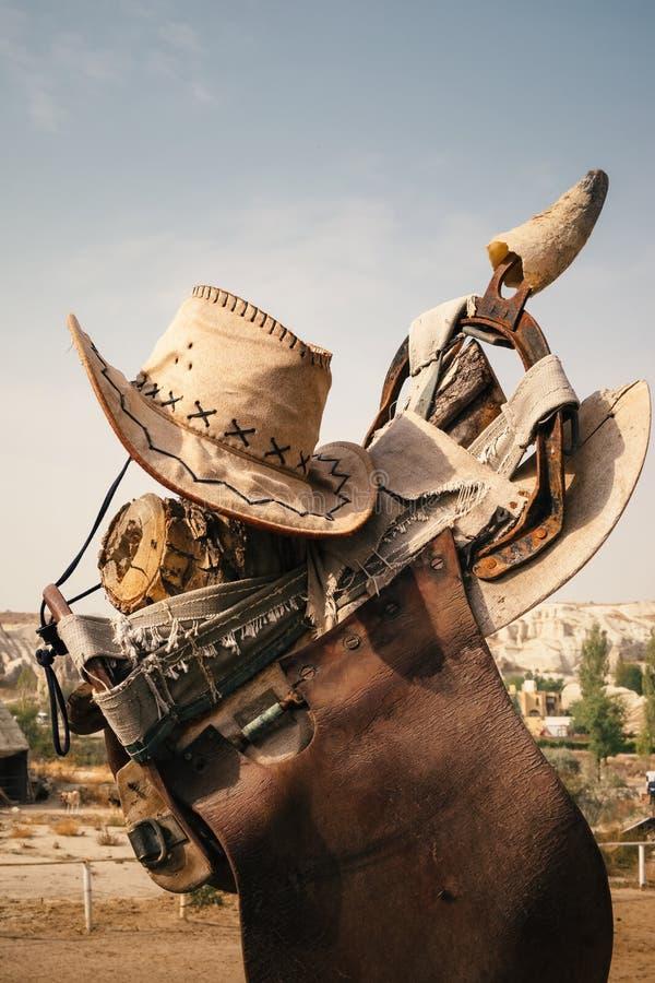 Cowboyhut und Pferdesattel auf dem Bauernhof lizenzfreie stockbilder