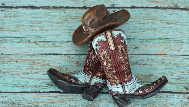 Cowboykängor och hatt på en krickabakgrund royaltyfri foto