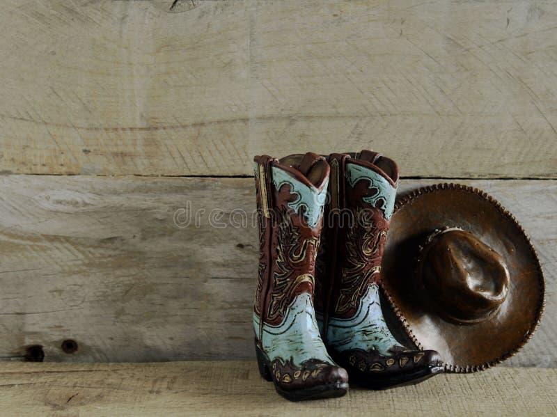 Cowboykängor och hatt på träbakgrund royaltyfria foton