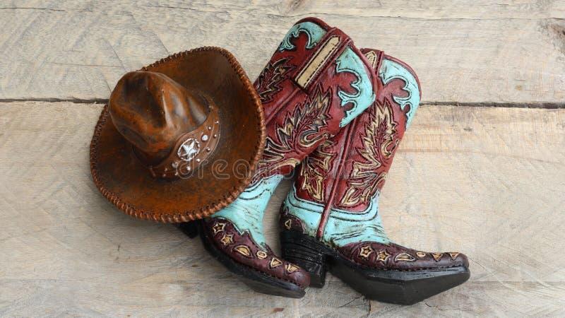 Cowboykängor och hatt på träbakgrund royaltyfri foto