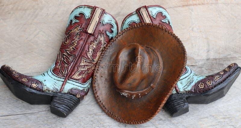 Cowboykängor och hatt på träbakgrund royaltyfri bild